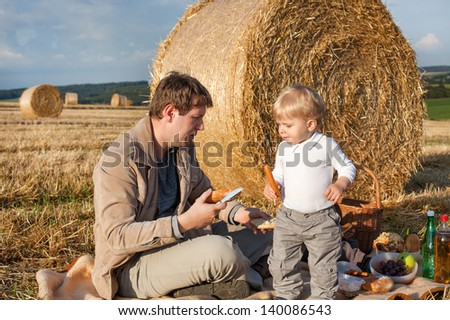 Young man and little toddler boy making evening picnic on hay field, Germany. - stock photo