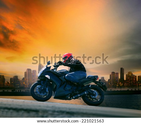 young man and safety suit riding big motorcycle against beautiful dusky sky and urban scene with copy space - stock photo