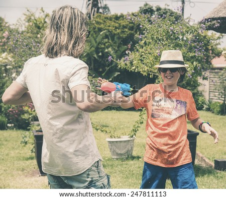 Young man and teenage boy playing with water gun in garden. - stock photo