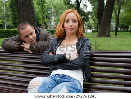 Young man and woman angry and conflicting on a park bench - stock photo