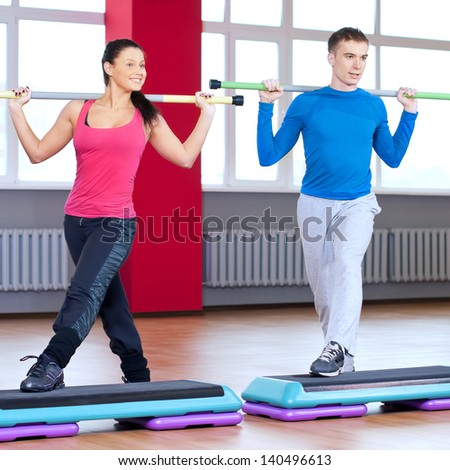 Young man and woman at the fitness gym is doing stretching exercises - stock photo