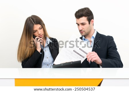 Young man and woman at work as receptionist in hospital talking on the phone for appointment. - stock photo
