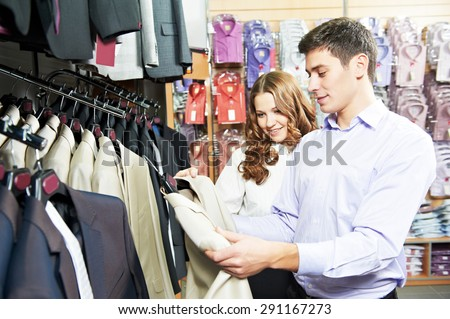 Young man and woman choosing suit jacket during apparel shopping at clothing store - stock photo