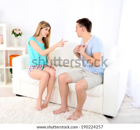 Young man and woman  conflict sitting on sofa argue unhappy, on home interior background - stock photo