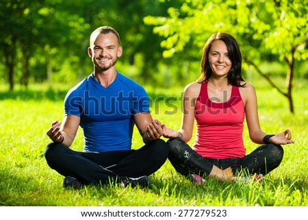 Young man and woman doing yoga in the sunny summer park. Couples Yoga on green grass outdoor. - stock photo