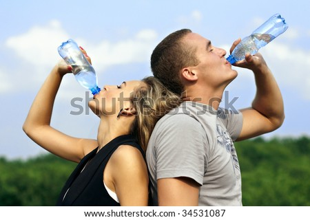 Young man and woman drinking water from a bottle - stock photo