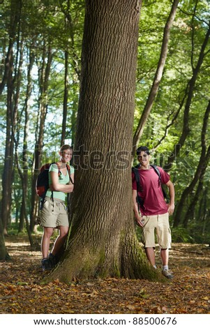 young man and woman during hiking excursion, posing near large tree and smiling. Vertical shape, front view, full length - stock photo