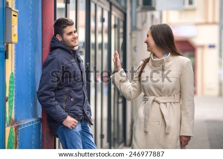 Young man and woman flirting on the street - stock photo
