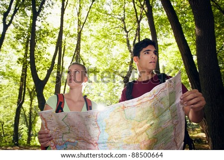 young man and woman got lost during hiking excursion and look for destination on map. Horizontal shape, waist up - stock photo