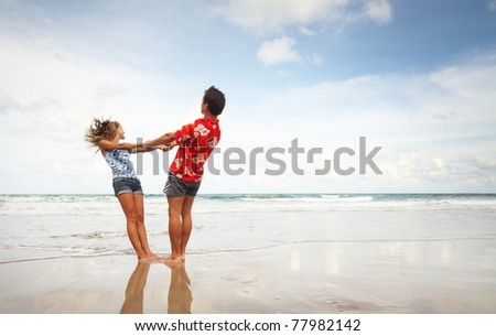 Young man and woman having fun on wet sand at sunny day - stock photo