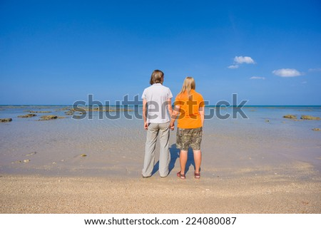 Young man and woman holding hands on island beach during low water - stock photo