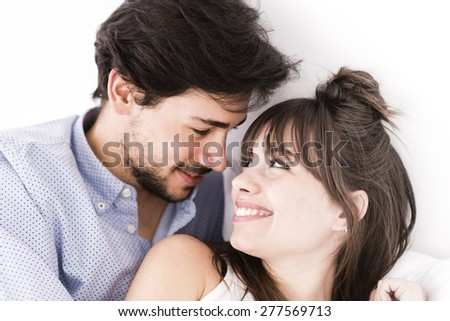 Young man and woman in bed. Couple at white background. - stock photo
