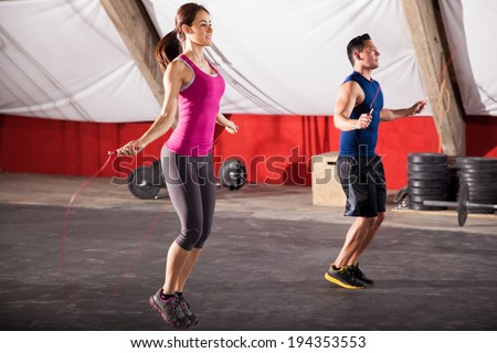 Young man and woman jumping ropes as part of their workout in a gym - stock photo