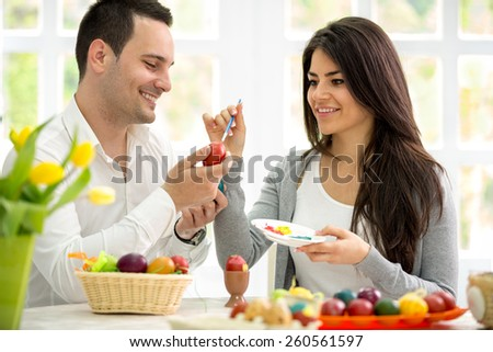 Young man and woman painting Easter eggs, couple in love on Easter - stock photo