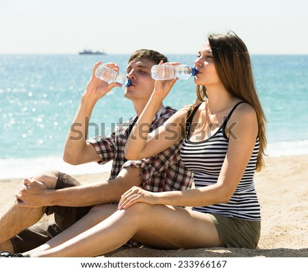 Young man and woman relaxing on the beach and drinking bottled water - stock photo