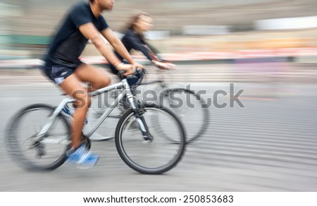 Young man and woman riding bicycles on a city street.  Intentional motion blur - stock photo