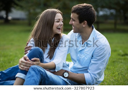 Young man and woman sitting, hugging and laughing in park on the grass in autumn or summer. Family looking at each other - stock photo