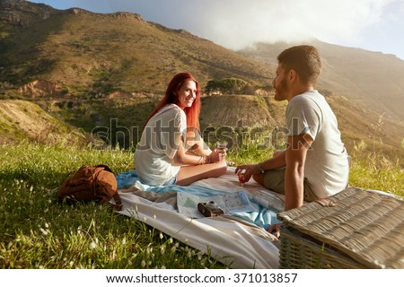 Young man and woman sitting on the grass during a picnic with glass of wine. Loving young couple having a conversation while on countryside holiday, with mountain range view in background. - stock photo