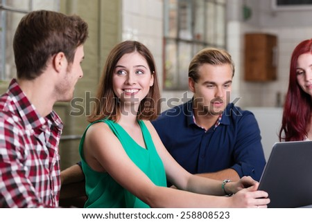 Young man and woman smiling and feeling attracted to each other while sitting at a table next to their young colleagues, in front of a laptop, indoor - stock photo