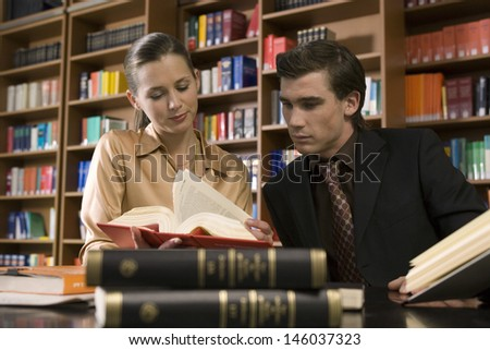 Young man and woman studying at desk in the library - stock photo