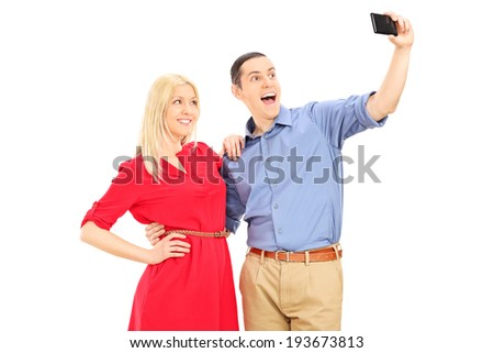Young man and woman taking a selfie with cell phone isolated on white background - stock photo