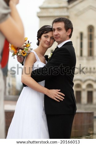 Young man and woman taking wedding photos in front of a cathedral - stock photo