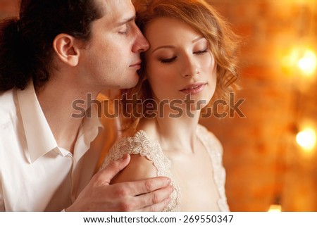 Young man and woman together over brick red wall and lights - stock photo
