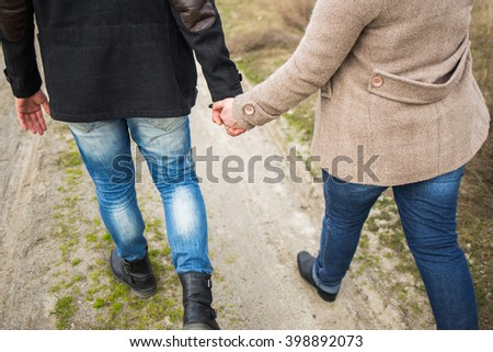 Young man and woman walking along countryside road holding hands. Couple in love having a walk on cold spring or autumn day. People dressed in warm clothes coats and denim jeans. - stock photo