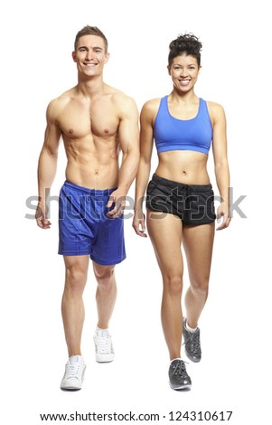 Young man and woman walking in sports outfits on white background smiling - stock photo