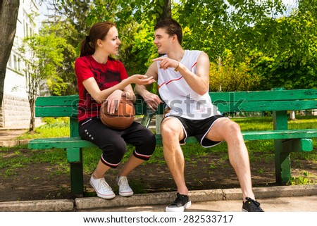 Young Man and Woman Wearing Athletic Clothing Sitting on Green Park Bench with Basketball Having a Conversation or Argument After the Game - stock photo