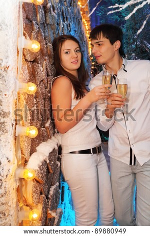 Young man and woman wearing white shirts with glasses of champagne stand near stack of wood - stock photo