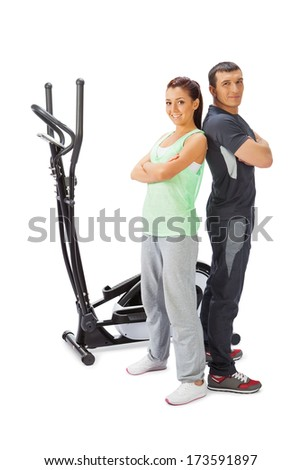 Young man and woman with elliptical cross trainer. - stock photo