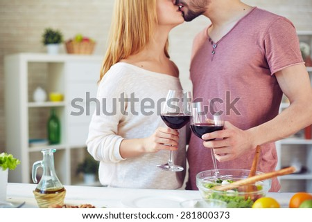 Young man and woman with red wine kissing in the kitchen - stock photo