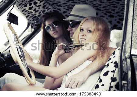 Young man and women driving retro car - stock photo