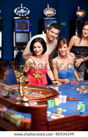 young man and women smiling and playing roulette - stock photo