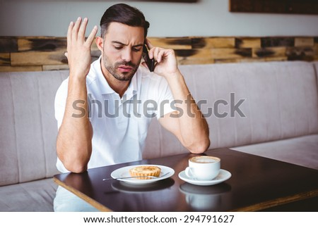 Young man angry on the phone at the cafe - stock photo