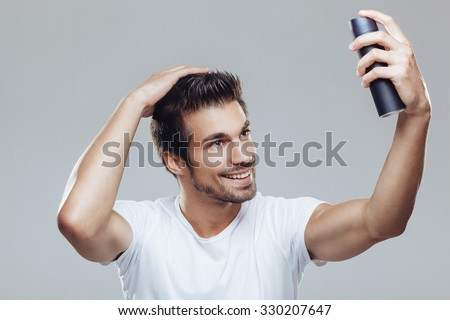 Young man applying hair spray to his hair - stock photo