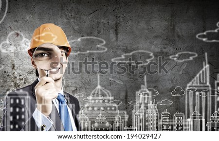 Young man architect against sketch background looking in magnifying glass - stock photo