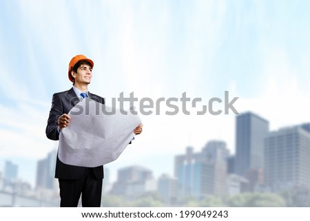 Young man architect looking at construction project - stock photo