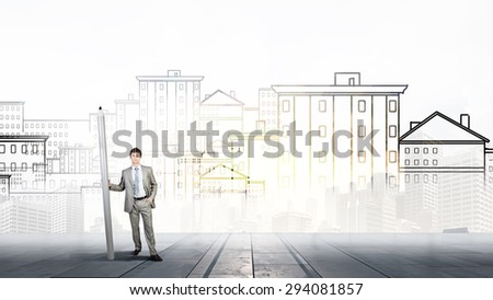 Young man architecture designer with huge pencil - stock photo