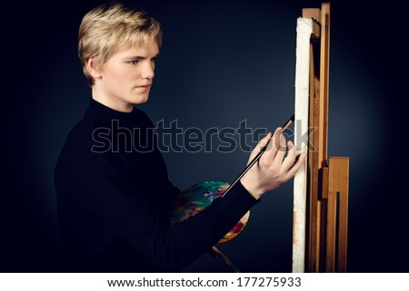 Young man artist paints on canvas with oil paints. Studio shot over black background. - stock photo