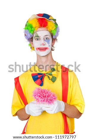 Young man as clown holding pink plastic flower - isolated - stock photo