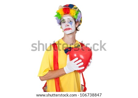 Young man as clown with red balloon - stock photo
