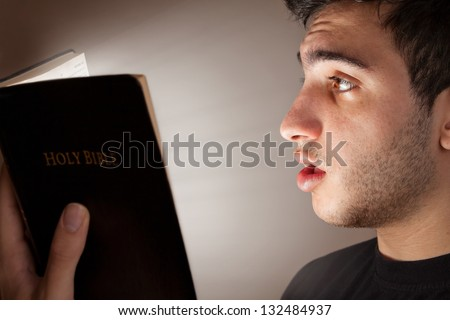 Young man astonished and intrigued by open Bible - stock photo
