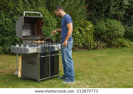 Young man at a barbecue grill - stock photo