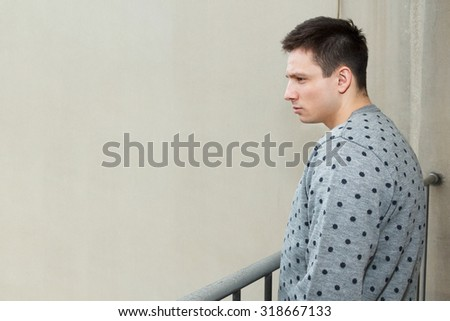 Young man at balcony in depression suffering emotional crisis. Attractive male model looking down from balcony. Person on terrace looks to somber and desolate city after rain. Stalker watching someone - stock photo