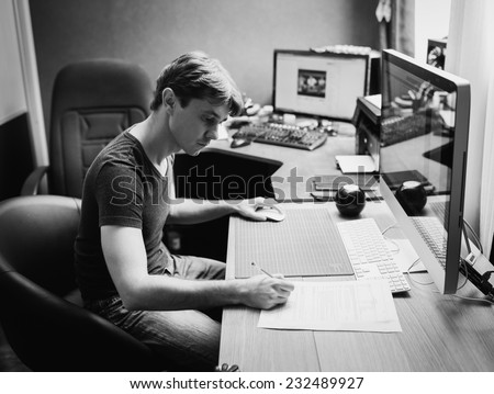 Young man at home using a computer, freelance developer and designer working at home, black and white photo - stock photo