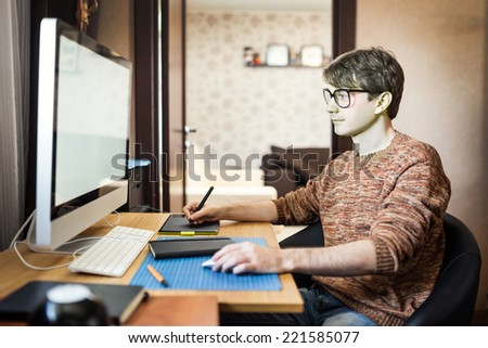 Young man at home using a computer, freelance developer or designer working at home.  - stock photo