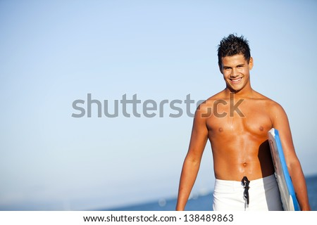 Young man at the beach with a boogie board - stock photo