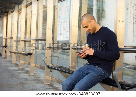 young man at the bus stop with a coffee and phone - stock photo
